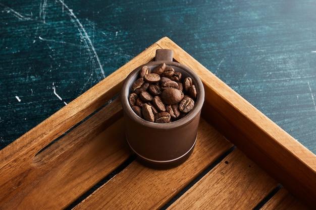 Grãos de café em uma xícara marrom.
