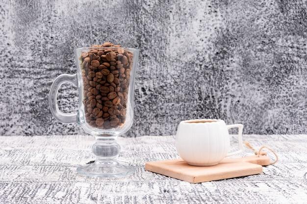 Grãos de café em vidro e uma xícara de café saboroso na superfície
