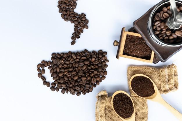 Grãos de café em xícara de café em forma com moedor de madeira e saco