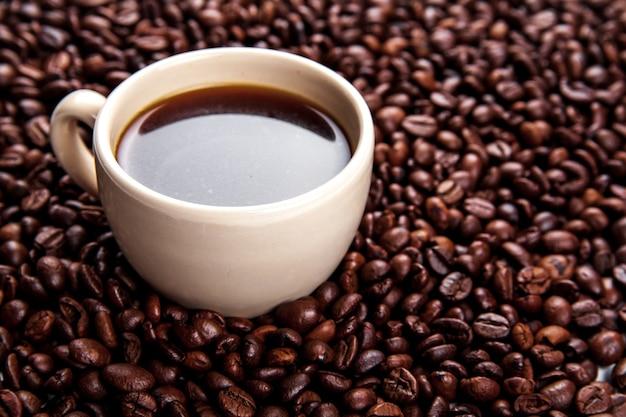 Grãos de café em xícara de café isolados