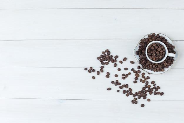 Grãos de café em xícara e pires vista superior em um fundo de madeira