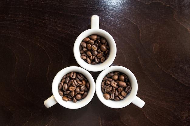 Grãos de café em xícaras brancas