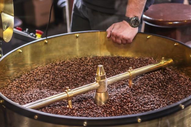 Grãos de café escuros e aromáticos em uma moderna máquina de torrefação