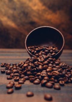 Grãos de café escuros em uma tigela sobre uma mesa marrom