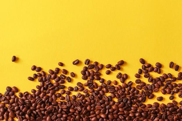 Grãos de café espalhados aleatoriamente sobre fundo amarelo.