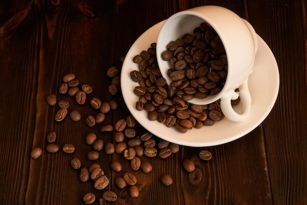 Grãos de café espalhados de uma xícara de porcelana branca sobre um fundo escuro de madeira