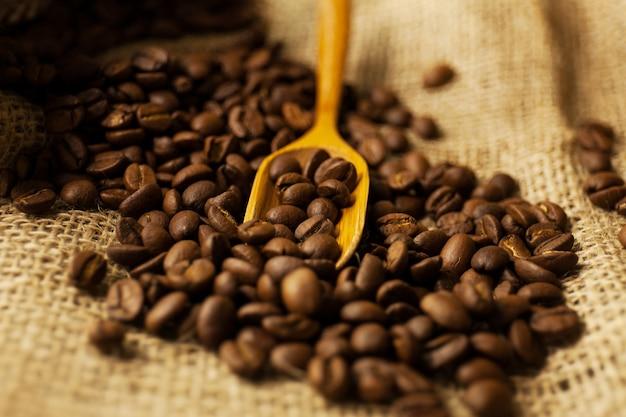 Grãos de café espalhados derramando de um saco de aniagem e uma colher