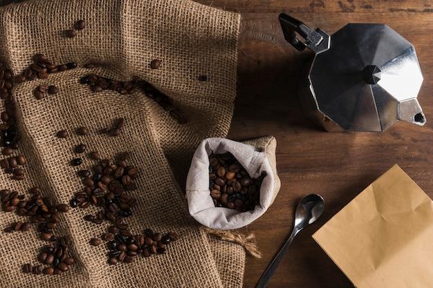 Grãos de café espalhados em pano de saco perto de saco, cafeteira e pacote
