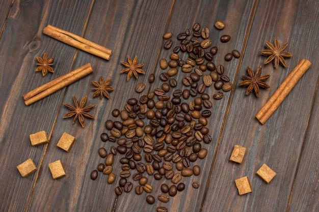 Grãos de café espalhados na mesa, anis estrelado, paus de canela e pedaços de açúcar mascavo.