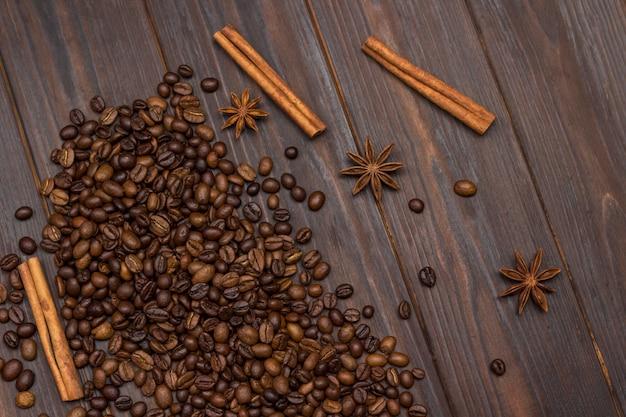 Grãos de café espalhados na mesa, anis estrelado, paus de canela