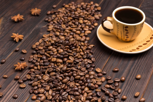 Grãos de café espalhados na mesa e anis estrelado. xícara de café.