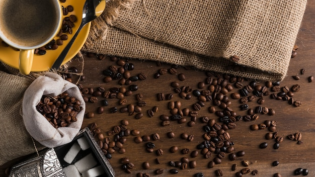 Grãos de café espalhados perto do copo, caixa de açúcar e pano de saco