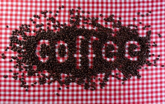 Grãos de café formando a palavra café em um fundo xadrez vermelho e branco.