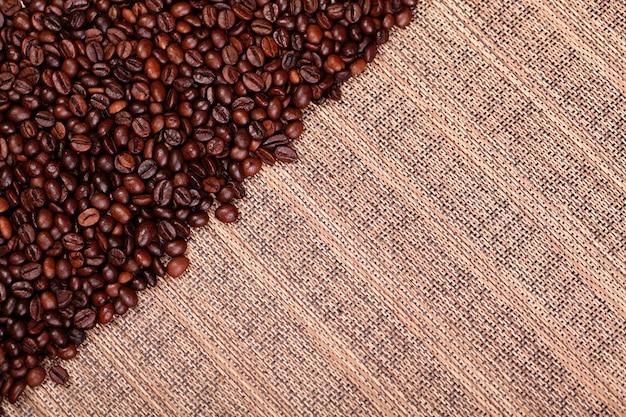 Grãos de café frescos em fundo de madeira