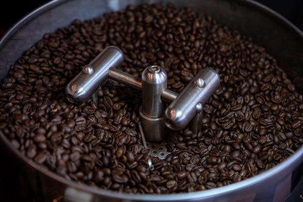 Grãos de café frescos no processo de tambor inoxidável na torrefação em foco escuro e seletivo. feijão de café torrado na hora em uma máquina profissional de refrigeração giratória. bandeja de resfriamento elétrica industrial.