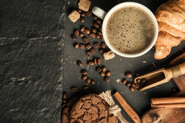 Grãos de café fritos pretos no café com biscoito e bolo no plano de fundo texturizado escuro