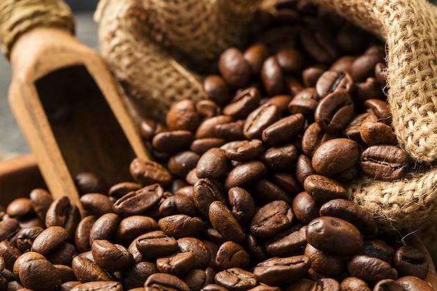 Grãos de café fritos pretos no plano de fundo texturizado escuro