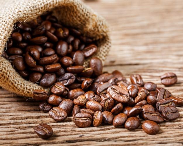 Grãos de café. grãos de café e saco em madeira velha