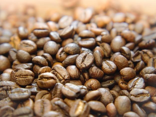 Grãos de café inteiros em fundo de madeira.