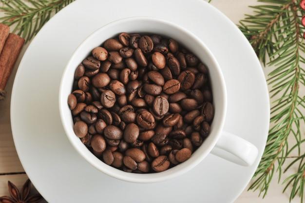 Grãos de café inteiros são derramados em uma xícara de café