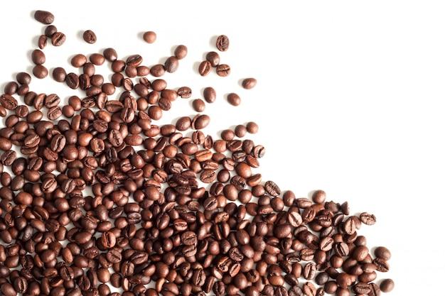 Grãos de café isolados na vista superior de fundo branco, copie o espaço