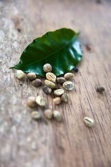 Grãos de café kopi luwak e folha na mesa de madeira