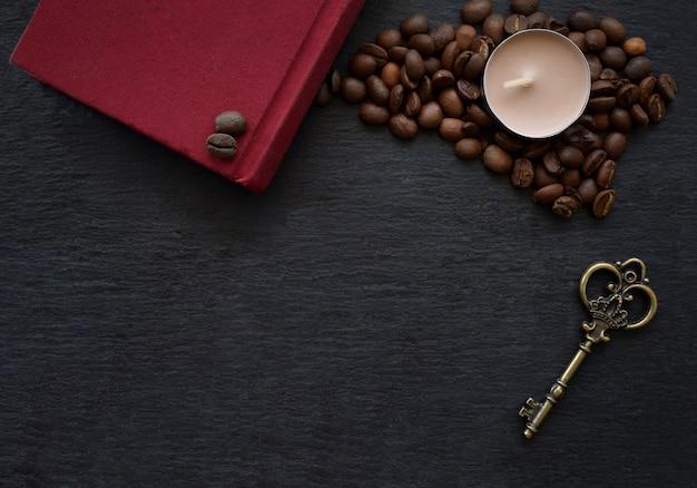 Grãos de café, livro vermelho e vela na mesa preta