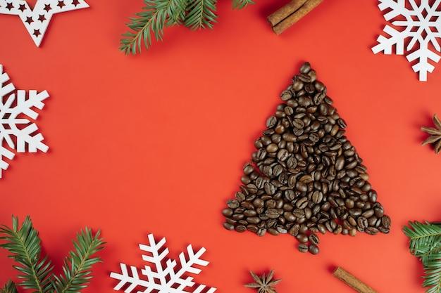 Grãos de café marrons dispostos em forma de árvore de natal com ramos de abeto e flocos de neve de madeira sobre fundo vermelho. postura plana. copie o espaço