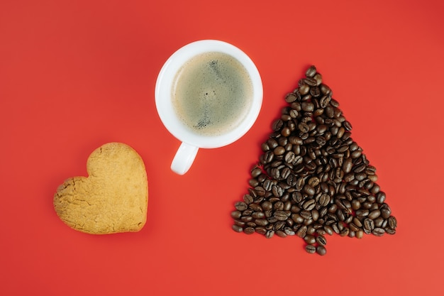 Grãos de café marrons dispostos em forma de árvore de natal com uma xícara de café e biscoito em forma de coração sobre fundo vermelho