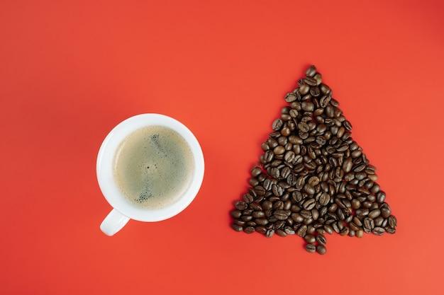 Grãos de café marrons dispostos em forma de árvore de natal com uma xícara de café sobre fundo vermelho. postura plana, copie o espaço