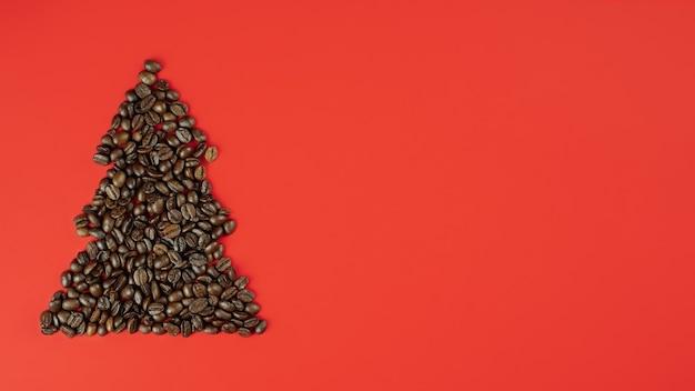 Grãos de café marrons dispostos em forma de árvore de natal em fundo vermelho. bandeira. postura plana, copie o espaço