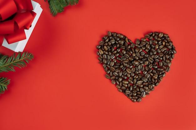 Grãos de café marrons dispostos em forma de coração com galhos de árvores de natal e caixa de presente em fundo vermelho, plana leigos