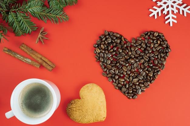 Grãos de café marrons dispostos em forma de coração com galhos de árvores de natal, xícara de café, biscoito em fundo vermelho