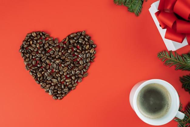 Grãos de café marrons dispostos em forma de coração com galhos de árvores de natal, xícara de café e caixa de presente em fundo vermelho