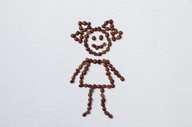 Grãos de café marrons dispostos em forma de menina. superfície isolada branca.