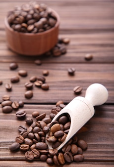 Grãos de café na colher de madeira em brown