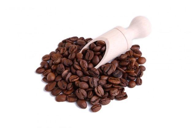 Grãos de café na colher de madeira, isolado no fundo branco.