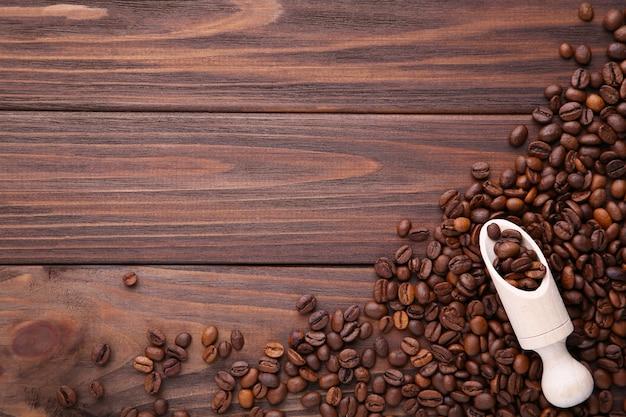 Grãos de café na colher de madeira no fundo marrom.