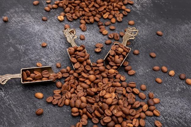Grãos de café na colher de metal na superfície escura
