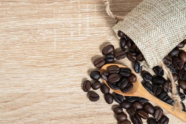 Grãos de café na colher de pau com fundo de mesa de madeira. vista superior com copyspace