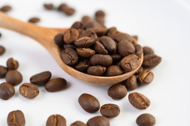 Grãos de café na colher de pau em uma mesa de madeira branca.