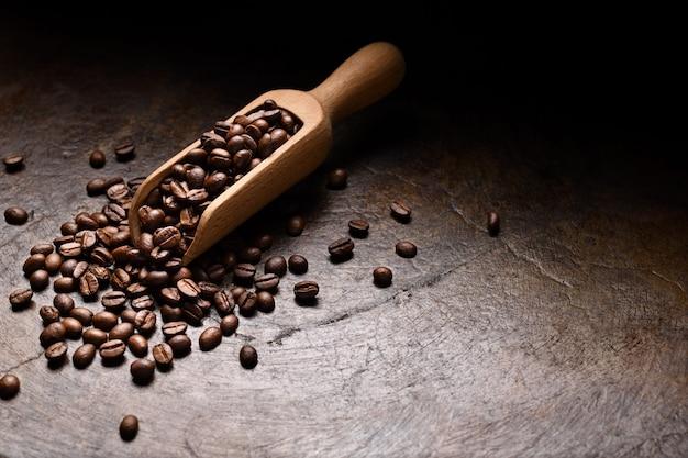 Grãos de café na colher de pau no fundo rústico