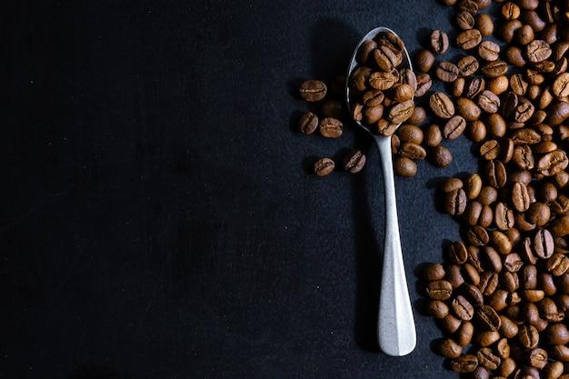 Grãos de café na colher. vista do topo. conceito de café.