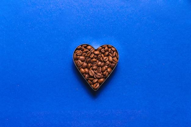 Grãos de café na forma de um coração sobre um fundo azul. vista do topo