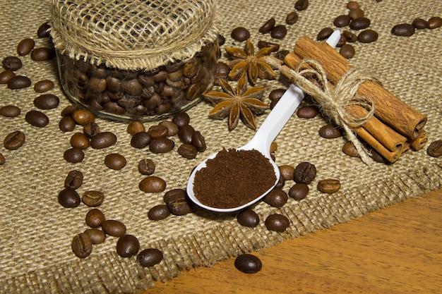 Grãos de café na panela, café moído em uma colher, canela, café torrado na sacaria