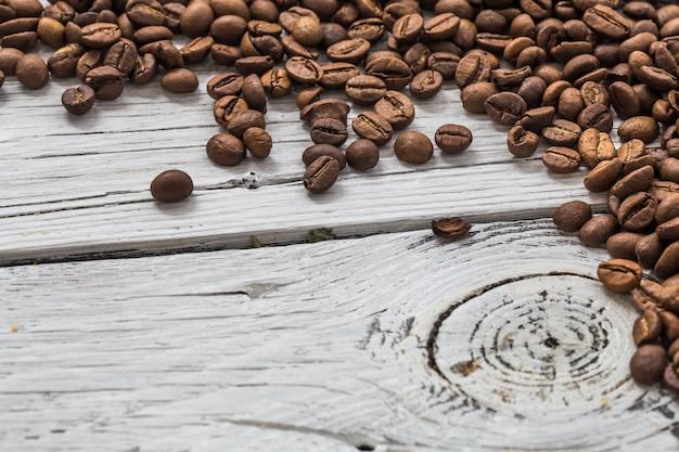 Grãos de café na parede de madeira branca, closeup