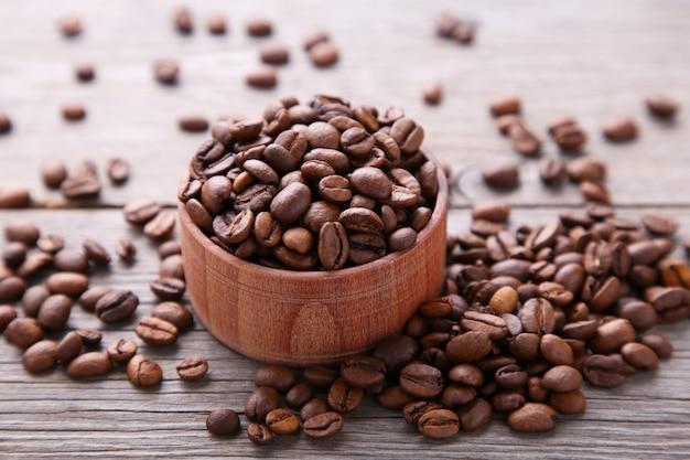 Grãos de café na tigela de madeira em cinza
