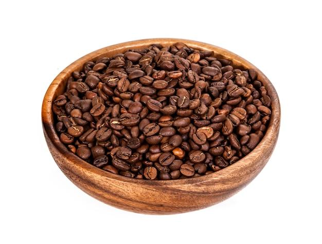 Grãos de café na tigela de madeira. isolado no branco