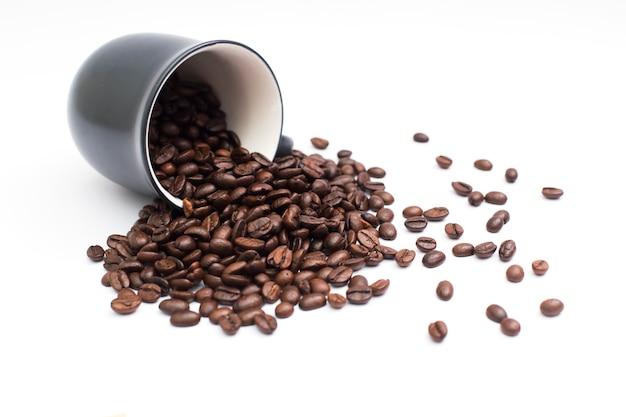 Grãos de café na xícara de café isolado no branco