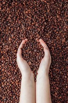 Grãos de café nas palmas das mãos em forma de coração no fundo do café